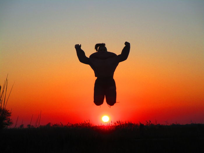 Silhouette girl jumping against sky during sunset