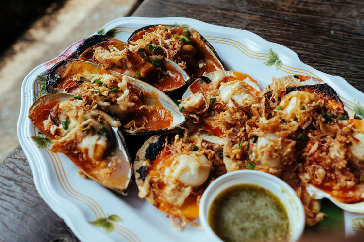 High angle view of baked mussels with cheese and garlic served on table