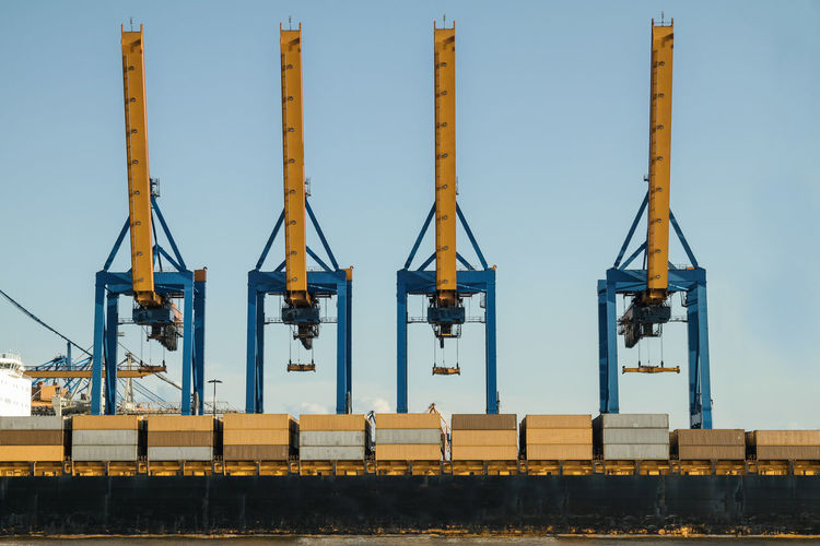 Commercial cranes in dock against clear sky
