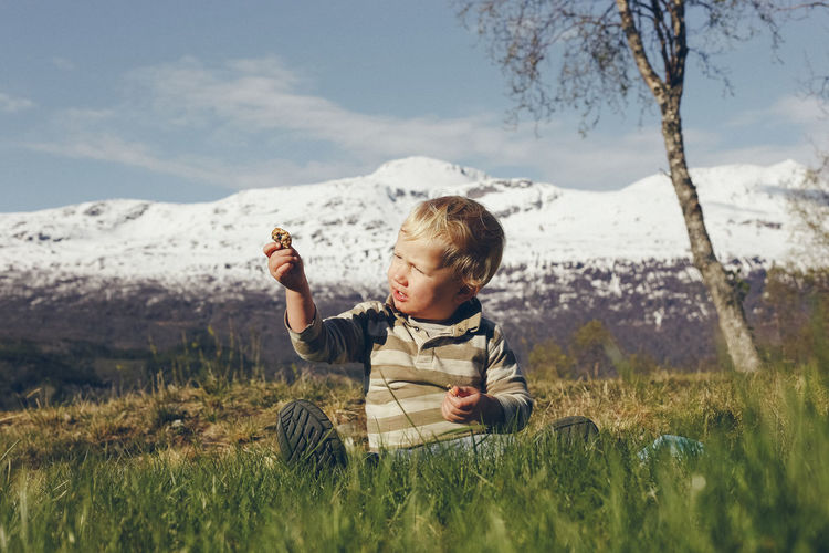 Cute boy holding stone while sitting on grassy land