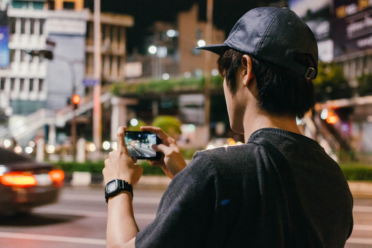Rear view of man photographing through phone on road at night