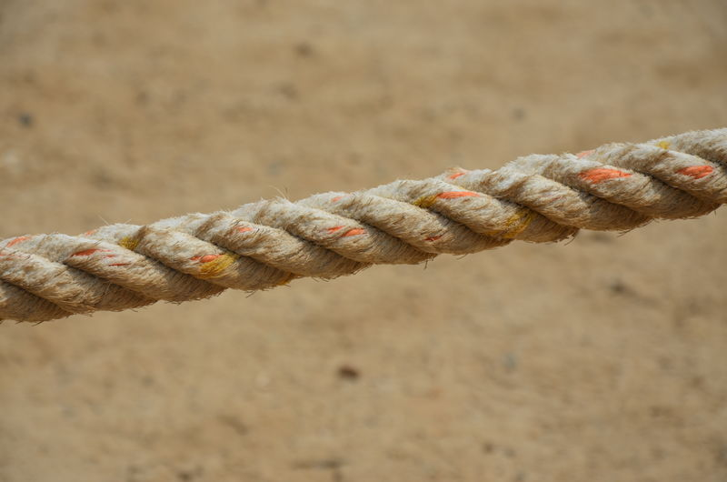 Close-up of rope tied to bollard on sand
