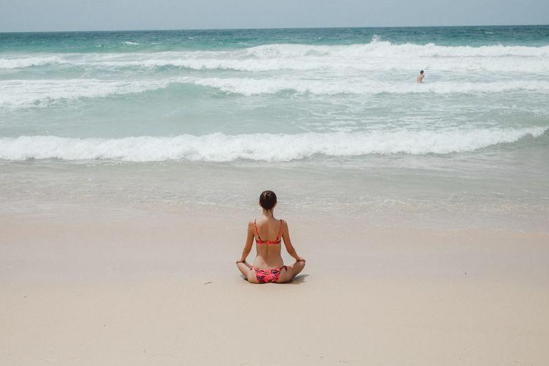 Rear view of woman in bikini meditating at beach