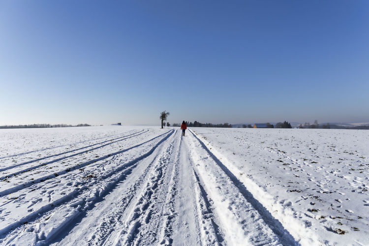 Rear View Of Person Walking On Snow Covered Field Against Clear Blue Sky