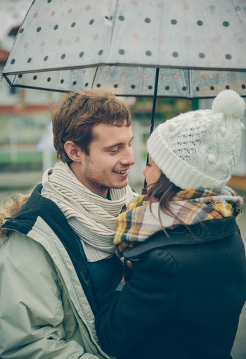 Portrait of young beautiful couple embracing under the umbrella in an autumn rainy day. Love and couple relationships concept. Woman Cold Winter Hat Scarf Rain Girl Young Female Outdoors Fall Real People Caucasian Two People Couple Love Realtionship Man Male Umbrella Rainy Happy Embracing Hugging Vertical