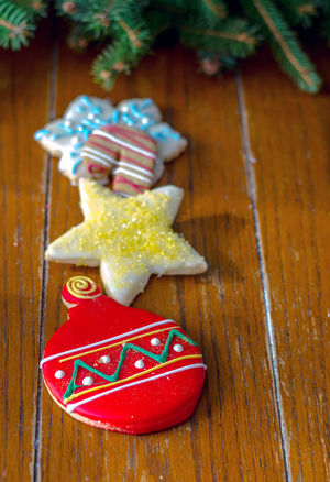 a stack of decorated Christmas cookies on a wood background Christmas Cookies For Santa Holiday Sweet Treats  Calories Candy Canes Celebration Event Christmas Cookie Table Colorful Decorative Cookies Food Greenery Iced Cookies Room For Text Season  Star Cookie Sugar Cookies Sweet Treat Holiday Moments