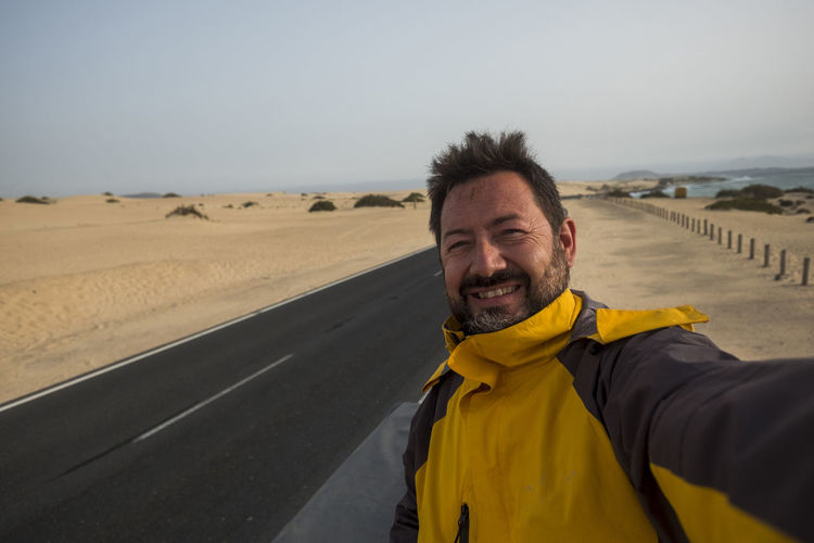 alternative vacation discovering the world for caucasian middle age man explorer taking selfie near a black asphalt long road cross the desert in Fuerteventura. enjoy life and lifestyle traveling the world One Person Portrait Smiling Looking At Camera Adult Leisure Activity Front View Happiness Real People Lifestyles Men Nature Road Standing Yellow Emotion Beard Day Sky Outdoors Arid Climate Adventure Fuerteventura Traveling Vacation