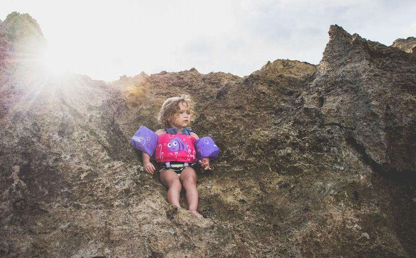 Portrait Of Girl On Rock Against Sky