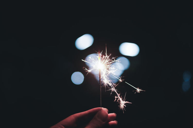 Close-up of human hand holding illuminated sparkler at night