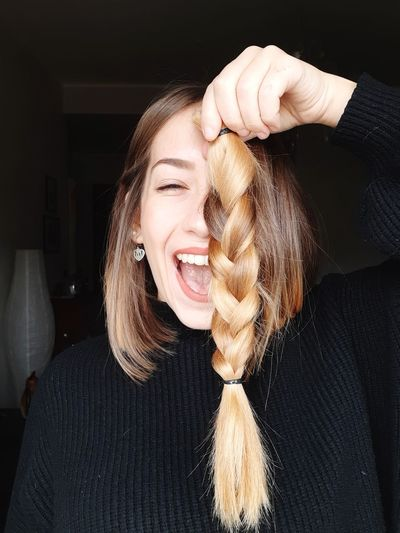 Portrait of smiling young woman holding braided cut hair