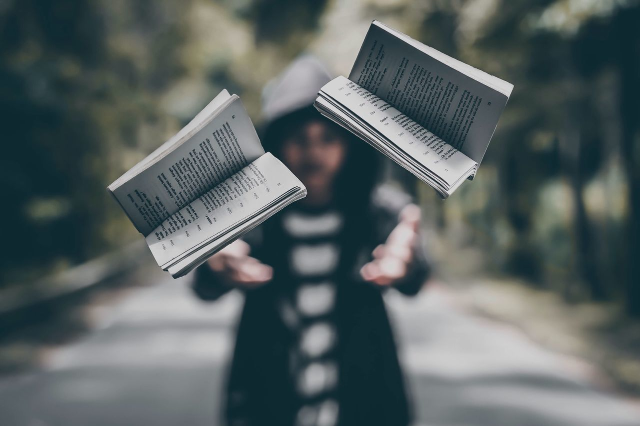 Man throwing books while standing on road