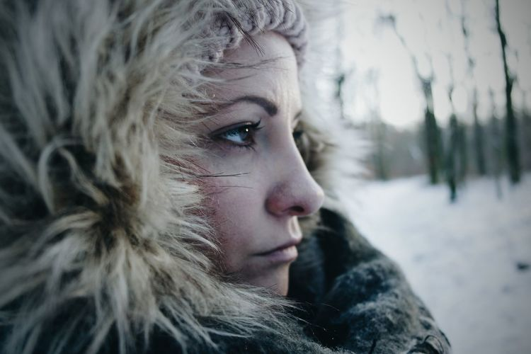 Close-Up Portrait Of Young Woman In Snow