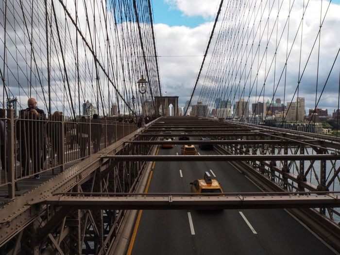 Over the bridge Brooklyn Bridge  New York Architecture Sky Built Structure Transportation Cloud - Sky Bridge Connection Bridge - Man Made Structure Mode Of Transportation Water Building Exterior Incidental People Outdoors Suspension Bridge Track City Nature Railing Travel Day