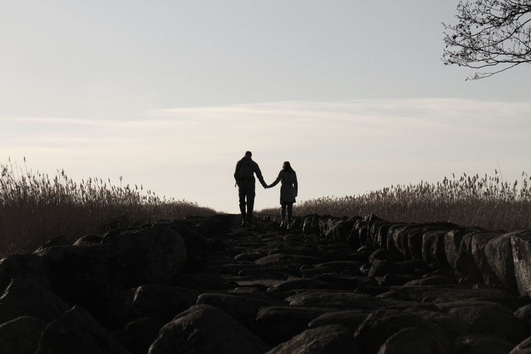 Rear view of silhouette couple holding hands while walking on rocks against sky during sunset