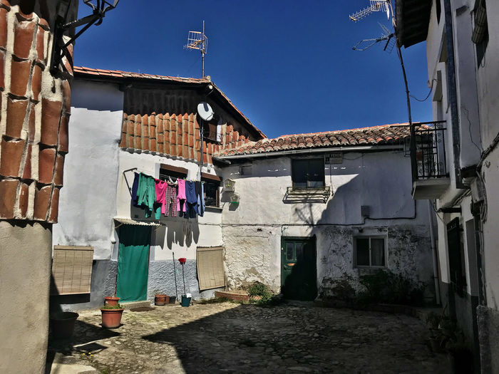 Building Exterior Architecture Built Structure Building Drying Laundry Hanging Residential District Clothesline Clothing Day House Nature City Sky Sunlight Window Outdoors People Wall Alley