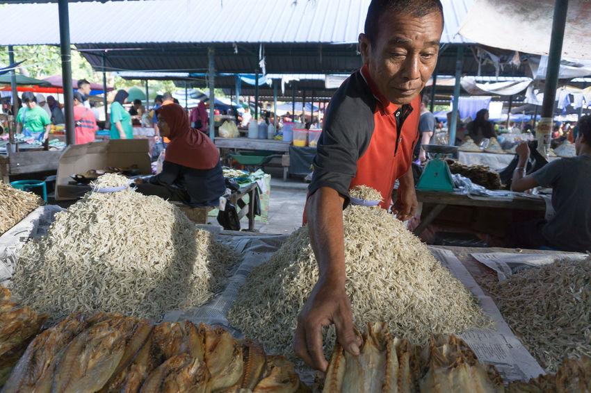 KOTA BELUD,SABAH,MALAYSIA-OCTOBER 23,2016: The seller of salt fish at sunday market Kota Belud,Sabah. Anchovy Food Freshness Kota Belud Lifestyles Men Occupation Salt Fish