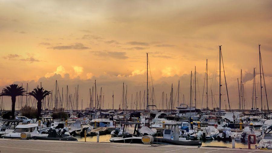 Sailboats moored at harbor during sunset