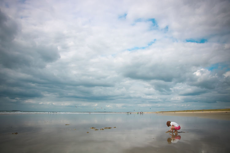 Girl digging sand at beach against cloudy sky