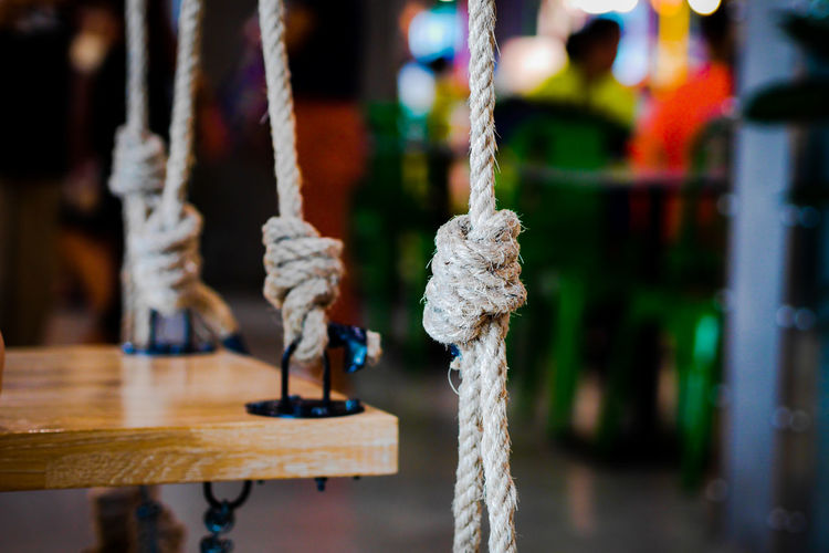 Close-up of swing hanging on rope