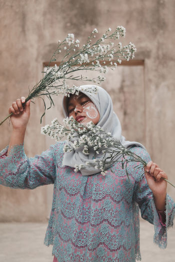 Woman Wearing Hijab Holding Flowers While Standing Against Wall