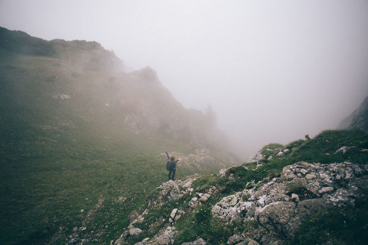 Woman standing on mountain against sky during foggy weather