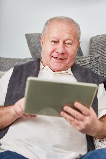 Midsection of man holding camera while sitting at home