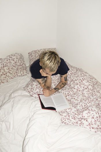 Woman reading book on bed at home