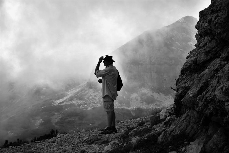 Full Length Of Man Standing On Mountain Against Cloudy Sky