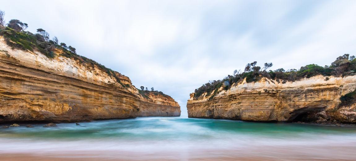 Panoramic shot of rocks in sea against sky
