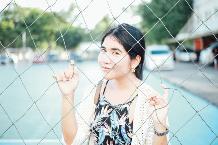 Portrait of young woman standing behind chainlink fence