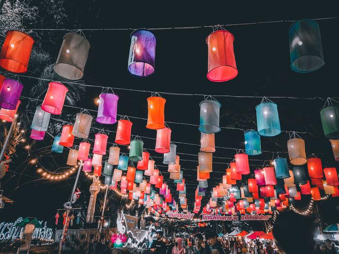Low angle view of illuminated lanterns hanging at store