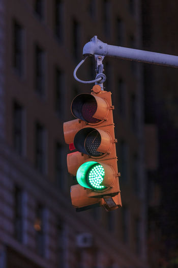 Go for it! Focus On Foreground Architecture Sign Building Exterior City Stoplight No People Built Structure Communication Outdoors Illuminated Safety Green Light Road Signal Close-up Hanging Light Day Guidance Security