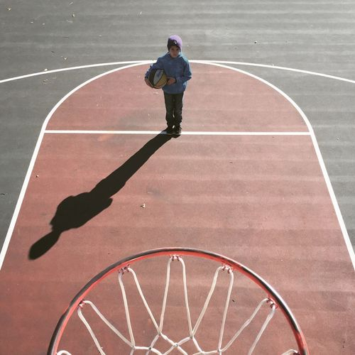High Angle View Of Boy Standing On Basketball Court
