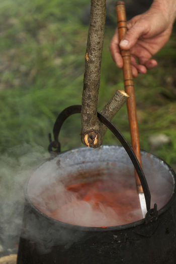 Cropped image of person preparing meat on barbecue grill