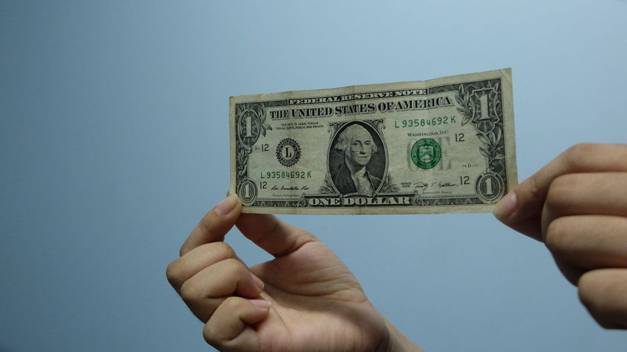 Cropped hands of woman holding paper currency against wall
