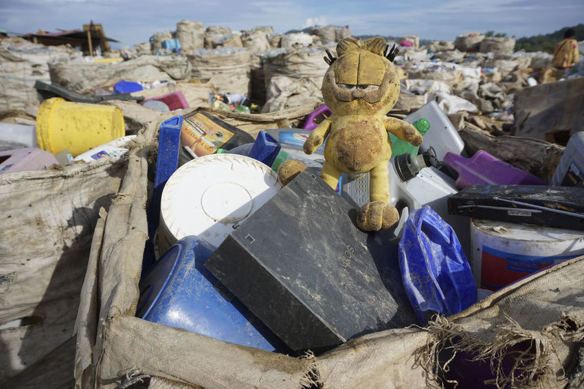 KOTA KINABALU, MALAYSIA - 09 JULY, 2017: An abandoned toy at the dumping site landfill. Bird Close-up Day DUMPING SITE Garfield Kid Landfill Waste No People Outdoors Poor  Sabah Borneo Toy