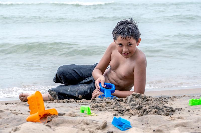 Portrait of shirtless boy sitting on beach
