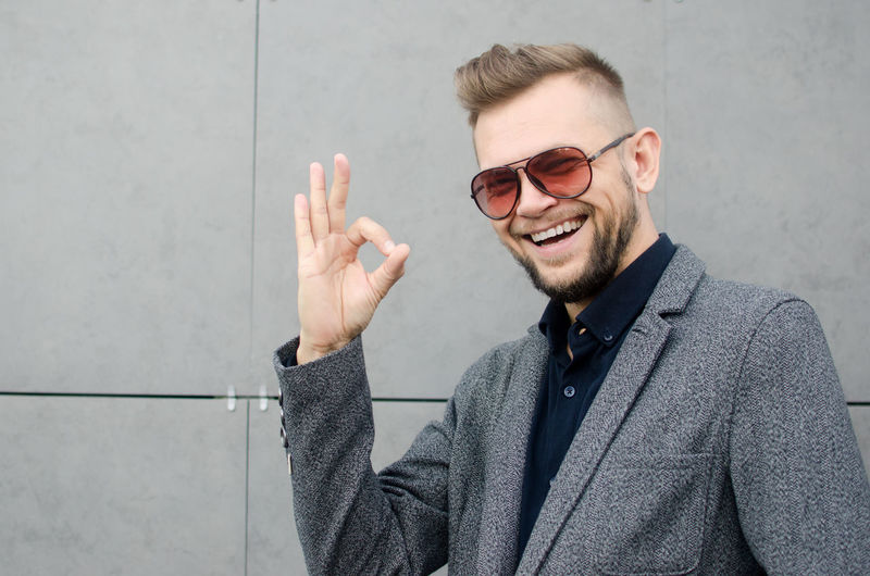 Portrait Of Cheerful Man Gesturing While Standing Against Wall