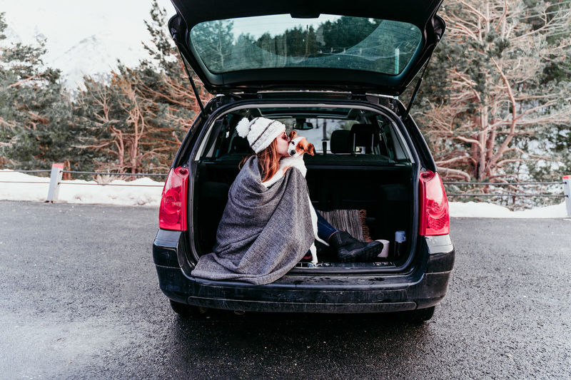 Woman kissing dog while sitting in car trunk