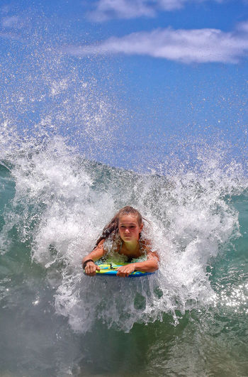 Young Woman Surfboarding In Sea Wave