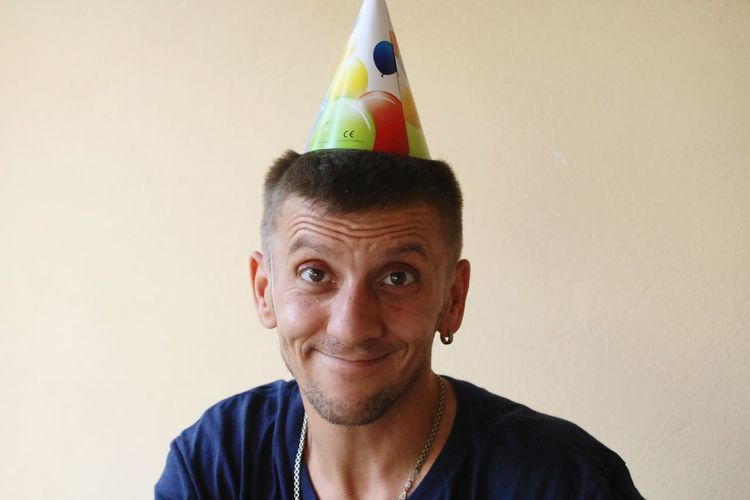 Portrait of man smiling while wearing party hat against wall