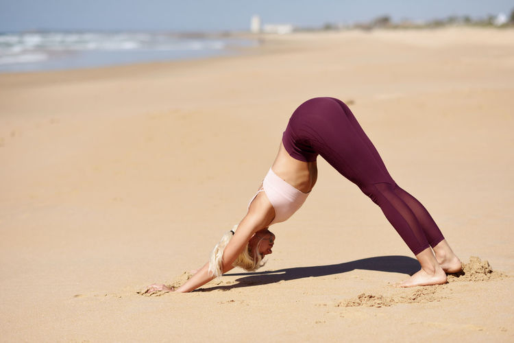 Caucasian woman practicing yoga at seashore. Young female doing downward-facing dog in the beach in Cadiz, Andalusia, Spain. Land Beach Sand One Person Full Length Lifestyles Adult Sea Nature Exercising Real People Day Women Healthy Lifestyle barefoot Leisure Activity Focus On Foreground Wellbeing Sport Hairstyle