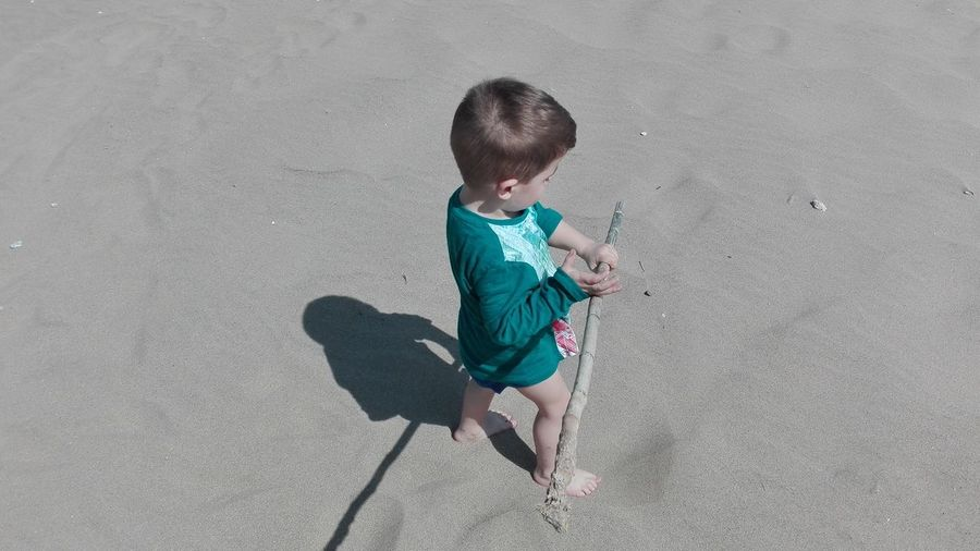High angle view of boy playing with stick on shore at beach