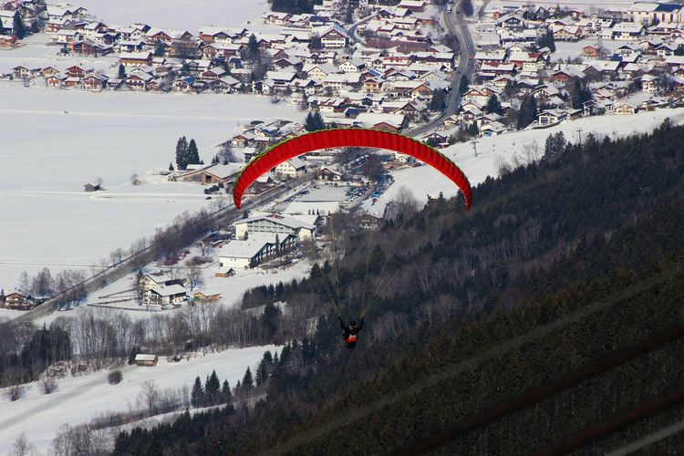 Man Paragliding Over Snow Covered Townscape