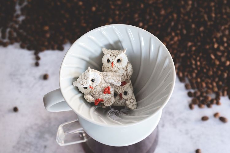 High angle view of toys in coffee filter on marble