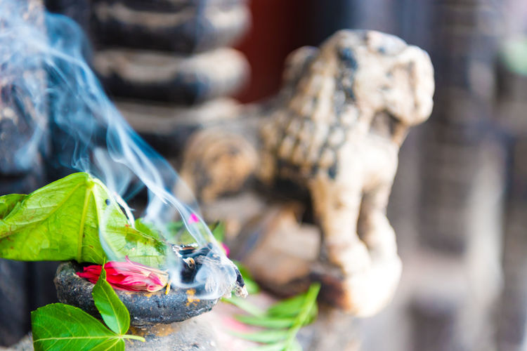 Close-up of burning incense by sculpture outdoors