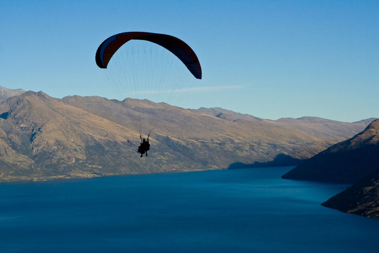 Person paragliding over lake and mountains against clear blue sky