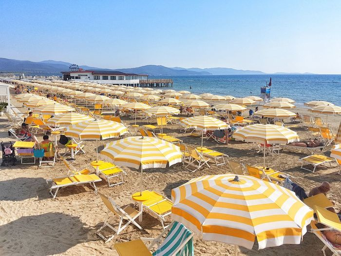 High angle view of parasols on beach against clear sky