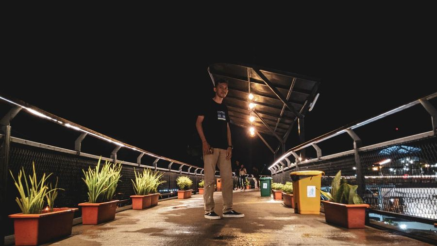 Man standing on bridge at night