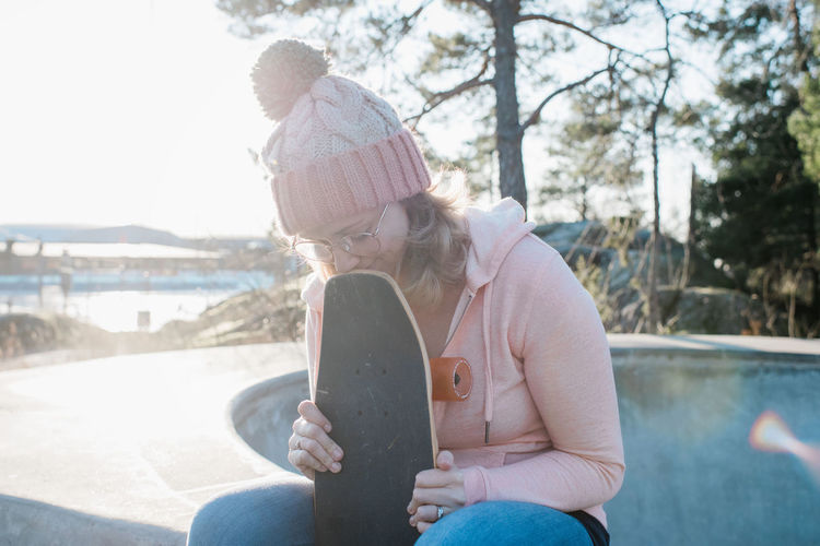 Midsection of woman sitting in park during winter